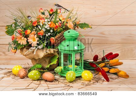 Easter Decorated Eggs And Candlestick With Spring Flowers On A Wooden Background