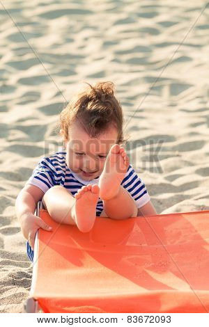 Playful Toddler Dressed As A Sailor Playing And Falling From A Sunbed On A Beach. Photo With Untradi