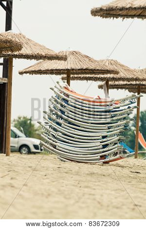 Straw Umbrellas And A Pack Of Sunbeds At A Beach. Photo With Untraditional Color Rendering For Artis
