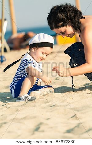 Sweet Smiling Toddler Dressed As A Sailor Sitting On A Beach And Exploring The Sand And Shells With