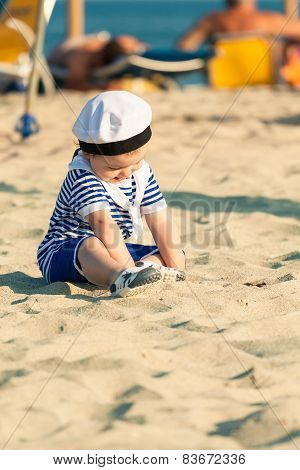 Sweet Smiling Toddler Dressed As A Sailor Sitting On A Beach And Playing With The Sand. Photo With U