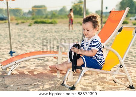 Sweet Toddler Dressed As A Sailor Sitting On A Beach Chair Near A Sunbed And Playing With His Sailin