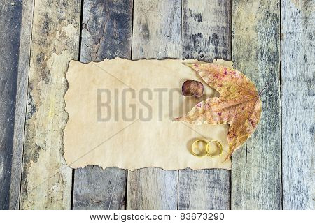 Close Up Gold Ring, Dry Leaves And Old Paper On Wooden Table