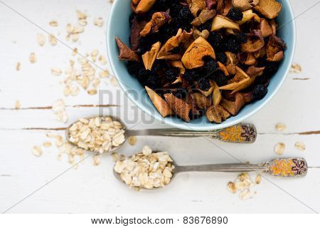 Two Tablespoons Of Oatmeal Lying On A White Wooden Background Near Blue Plate With Dried Apples And