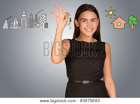 Woman making choice between city and country, holding keys in her hand