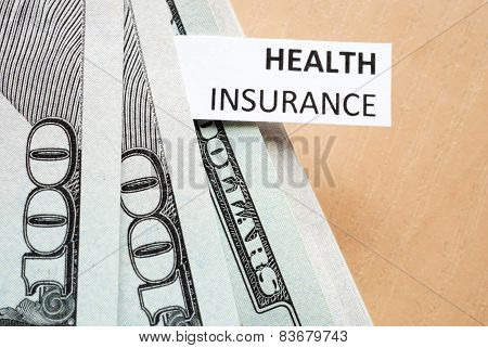 Paper with words Health insurance and money.