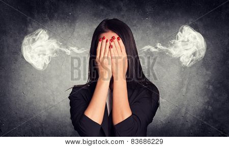Close-up portrait of businesswoman hiding face in her hands, with smoke from ears