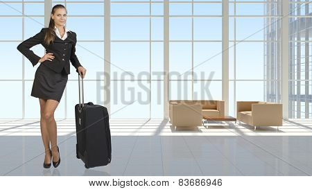 Businesswoman with travel bag in vast interior