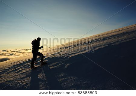girl goes on a snowy slope in the mountains against sun