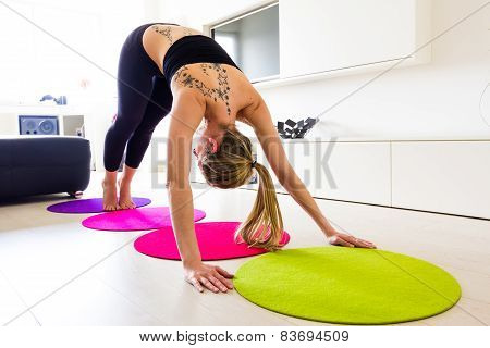 Young woman exercising and stretching her body in her living room.