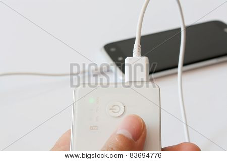 Male Hand Is Holding Power Bank Is Charging Smartphone