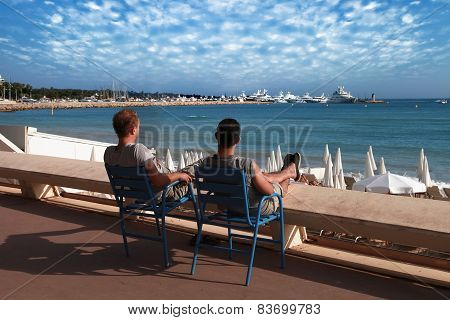 Cannes, France -  July 5, 2014: Two Friends Relaxing In Chairs.