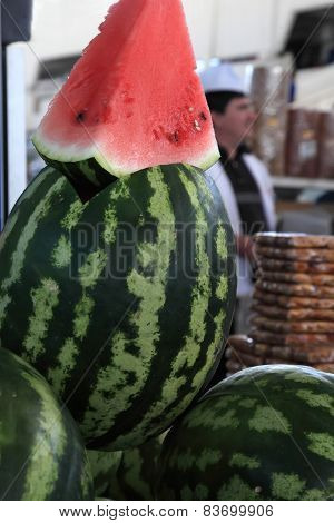 A Large Slice Of Watermelon Looking Out From The Middle Of The Watermelon