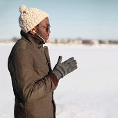 Portrait Of Stylish Young African Man Listening Music On Smartphone Outdoors In Winter Day