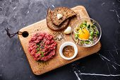image of tartar  - Beef tartare with salad and garlic toasts on dark marble background - JPG