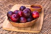 stock photo of satsuma  - Woven basket filled with satsuma plum with small bowl of plum jam in the back on wooden board photographed with natural light  - JPG