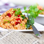 foto of tabouleh  - couscous with paprika on white plate close up  - JPG