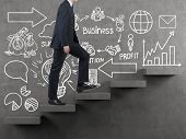 stock photo of climbing wall  - businessman walking on stairs and drawing business strategy on wall - JPG