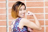 foto of skinny  - Smiling Skinny Asian American Woman Showing Biceps - JPG