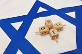 picture of hanukkah  - A white and blue Israeli Flag with the star of david on it with wooden dreidels for the Jewish holiday of Hanukkah - JPG