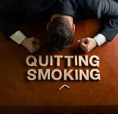 picture of quit  - Phrase Quitting Smoking made of wooden block letters and devastated middle aged caucasian man in a black suit sitting at the table - JPG