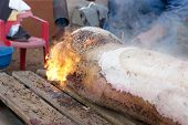 stock photo of slaughter  - Hair removal of the pig with blowtorch - JPG