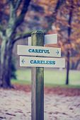 stock photo of dangerous situation  - Rustic wooden sign in an autumn park with the words Careful  - JPG
