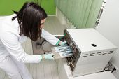 picture of pressure vessel  - Young Female Dentist Places Medical Autoclave For Sterilising Surgical And Other Instruments - JPG