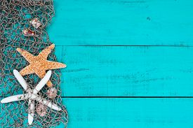 foto of shell-fishes  - Blank antique teal blue aged wood sign background with fish net border full of seashells and two starfish - JPG