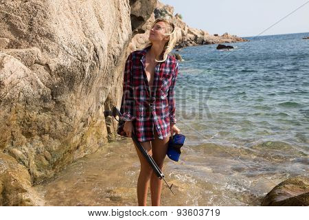 Girl With Harpoon In Flannel Shirt On The Rocky Beach.
