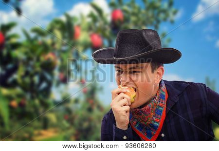 Young cowboy eating organic apple
