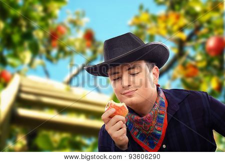 Happy cowboy tasting apple in orchard