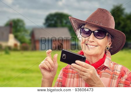 Old cowgirl surfing internet on smartphone in ranch