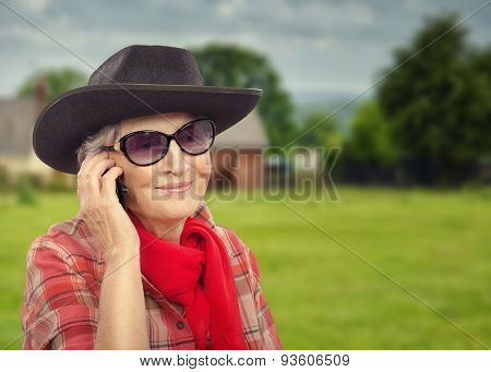 Aged rancher woman calling on cell phone