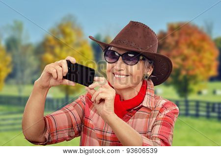 Aged cowgirl making selfie in front of ranch