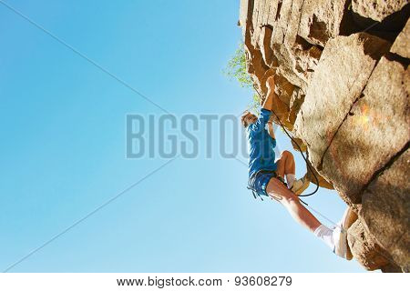 Young man in activewear climbing the rock