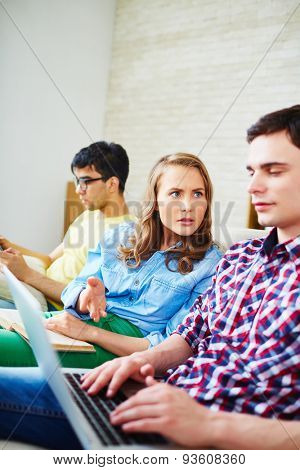 Modern guy using laptop while his girlfriend expressing displeasure with it
