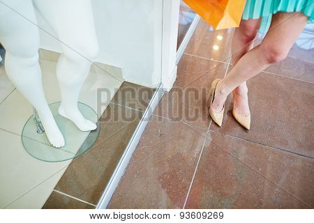 Legs of a shopper standing on the floor and those of mannequin in the shop window