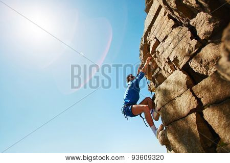 Young man climbing on top of rock