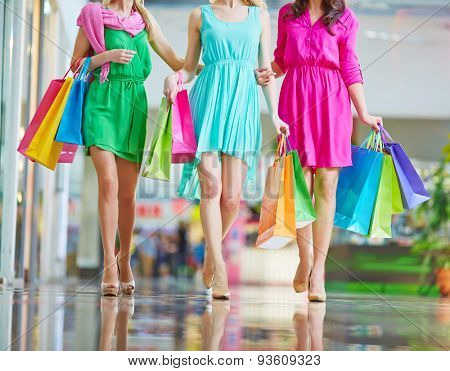 Group of shoppers in bright dresses carrying paperbags