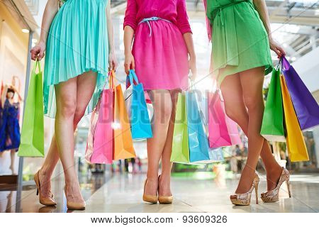Three girls in bright dresses standing in the mall