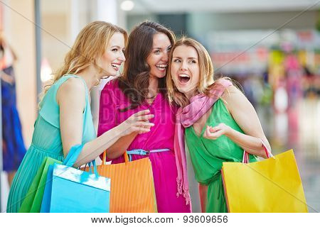 Charming shopaholics with paperbags discussing something the saw in the mall
