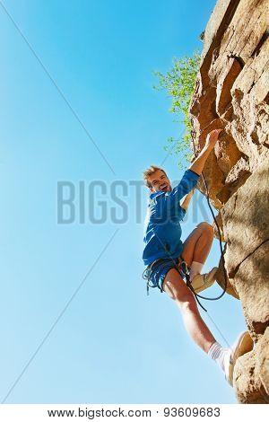 Young mountain climber reaching top of rock