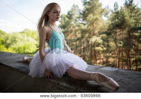 Graceful ballerina in white tutu sitting on the splits