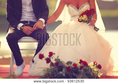 Bride And Groom Sitting And Holding Hands