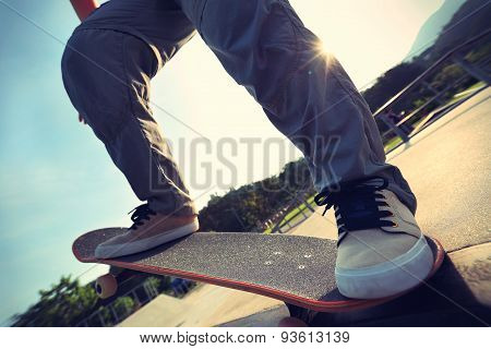 closeup of skateboarder legs riding skateboard at skatepark