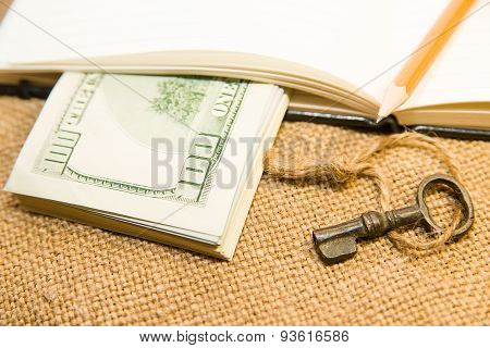 Opened Notebook, Pencil, Key And Money On The Old Tissue