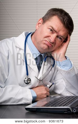 Bored Doctor Sits At Laptop