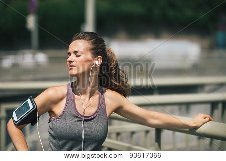 Woman Runner Taking A Break In The Sunshine Listening To Music