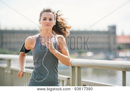 Smiling Woman Jogging In Urban Setting Listening To Music
